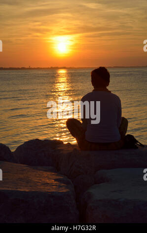 person on the cliff at sunset - Stock Image