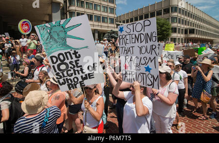 Boston, Massachusetts, USA. 30th June, 2018.  U.S. Demonstrators holding a signs in City Hall Plaza in Boston, MA during the Rally against Family Separation by the current United States administration. Rallies against U.S. President Donald Trump's policy of the detention of Central American and Mexican immigrants and immigrant families separated by U.S. customs and border agents (I.C.E.) took place all over the United States.  Credit: Chuck Nacke/Alamy Live News - Stock Image