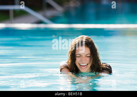 Young woman laughing in a swimming pool - Stock Image