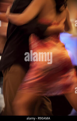 A closeup of a young man and woman dancing Milonga Tango in Argentina, low angle view, motion blur. - Stock Image
