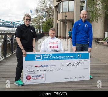 London, UK. 25th Apr 2019. David Weir poses with a cheque for £20,000   made payable to Wier Archer Academy during The London Marathon Wheelchair Athletes Photocall which took place outside the Tower Hotel with Tower Bridge in the background ahead of the Marathon on Sunday. Credit: Keith Larby/Alamy Live News - Stock Image