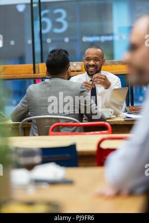 Businessmen talking, working in cafe - Stock Image