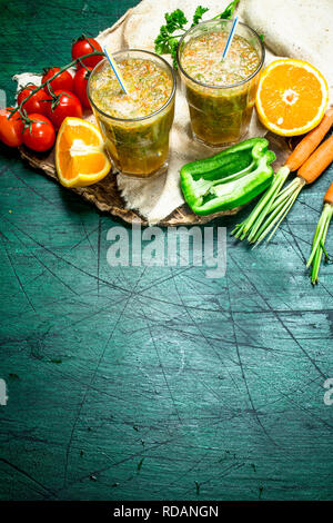Vitamin smoothie with tomatoes, sweet pepper, carrots and orange. On rustic background. - Stock Image