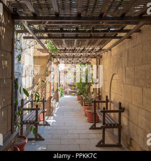 Passage ceiled with wooden pergola leading to the House of Egyptian Architecture historical building from the Mamluk era, Cairo, Egypt - Stock Image