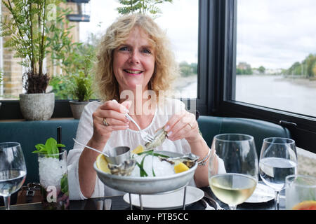 Middle aged mature woman eating oysters at the Rick Stein fish restaurant in Barnes London UK Photograph taken by Simon Dack - Stock Image