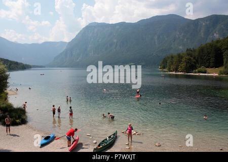 People enjoying the water at Lake Bohinj, Slovenia, Europe, in summer - Stock Image