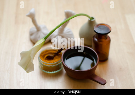 A table top arrangement of spice, oil and massaging tools, used in Ayurveda massage. - Stock Image