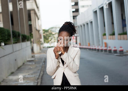 Young businesswoman standing outside and drinking coffee. - Stock Image