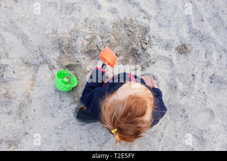 Small toddler is playing with a shovel in the sand on a playground - Stock Image