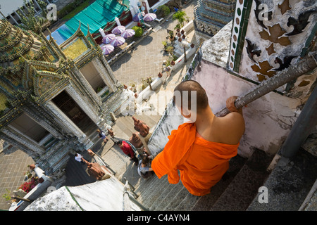 Thailand, Bangkok. A monk descends the steps of the prang (Khmer-style tower) at Wat Arun. - Stock Image