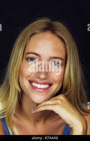 Young woman smiling cheerfully, portrait - Stock Image