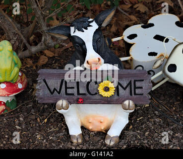 Garden ornament cow holding a welcome sign. - Stock Image