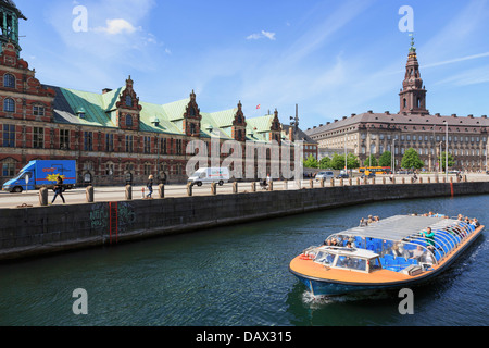 Tourists canal boat city sightseeing tour by Old Stock Exchange building Borsen and Christiansborg Palace in Copenhagen - Stock Image