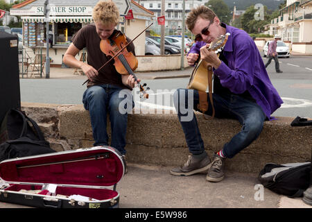 Buskers playing fiddle and guitar on promenade at Sidmouth Folk Festival 2014. - Stock Image