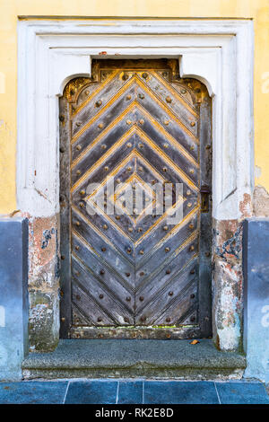 Baroque door in an old wall, decorative frame and a stone doorstep. Vintage entrance from solid wooden planks. Knocker and handle from rusty metal. - Stock Image
