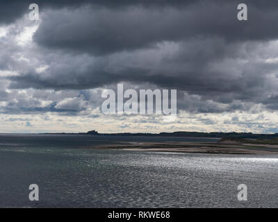 View of the Northumberland coast with a brooding sky. - Stock Image