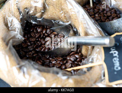 Close-up image of coffee beans in a hessian sack with a silver spoon on display at a farmer's market - Stock Image