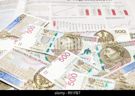 500 PLN banknotes on financial newspaper with bar graphs and charts - Stock Image