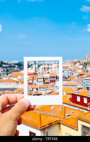 closeup of a young caucasian man with a white frame in his hand framing the tiled roofs of the old town of Porto, in Portugal, simulating an instant p - Stock Image