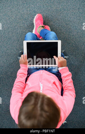 Girl 9 10 11 on an ipad with a blank screen copy space elementary school age - Stock Image
