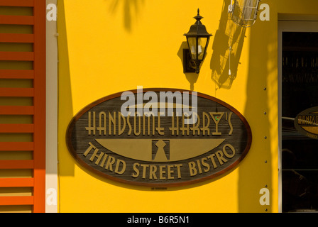 Handsome Harrys Third Street Bistro 3rd street st Sign Old Naples Florida fl bright yellow color palm tree shadow - Stock Image