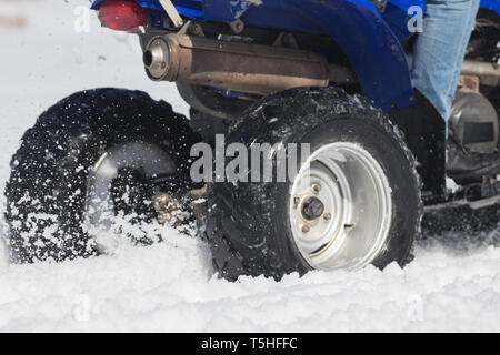A bright blue snowmobile in the forest in the snow - Stock Image