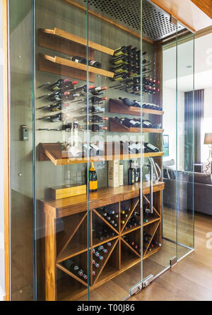 Clear glass constructed wine cellar with wooden shelves and racks filled with bottles inside a luxurious contemporary bungalow style home - Stock Image