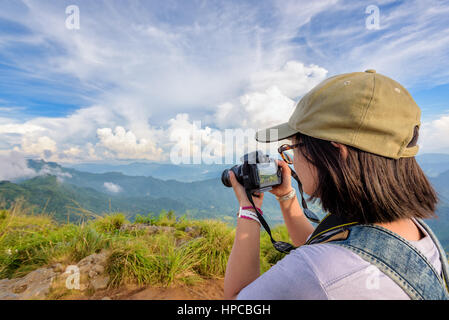 Hiker asian teens girl with backpack looking photo on digital camera is beautiful landscape natural of sierra and - Stock Image