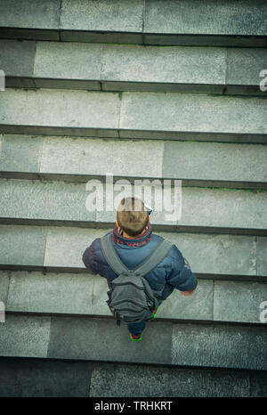 Man walking up a flight of concrete stairs viewed from above - Stock Image