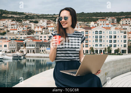 Portrait of a positive smiling young woman working on a laptop and drinking coffee outdoors. Freelancer or blogger or other. - Stock Image