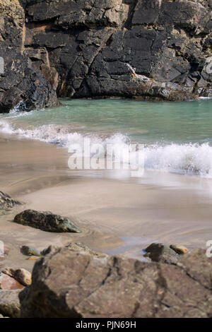 Waves gently rolling onto a beach in Pembrokeshire, Wales - Stock Image