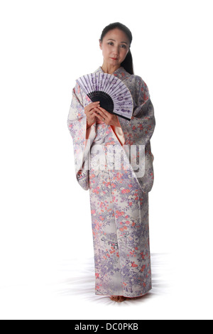 Japanese Lady Wearing a Pink and Lilac Patterned Kimono and Holding a Fan - Stock Image