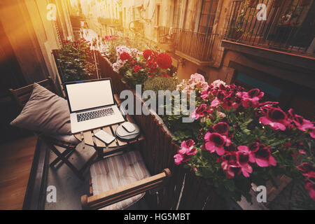 Small cozy beautiful workspace on balcony with laptop, smartphone and two chairs and a lot of flowers around on - Stock Image