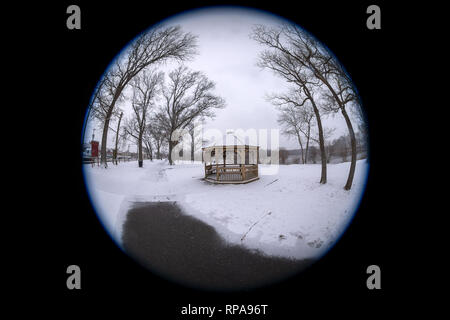 Long Island, New York, USA. 20th Feb, 2019. Snow falls at Mill Pond Park, with path partly plowed clear leading to wood gazebo and bare trees, on Long Island. 180 degree fisheye view of Nassau County public park. Credit: Ann E Parry/Alamy Live News - Stock Image