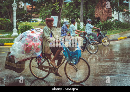 People on mopeds and bicycles transporting passengers and goods through the rainy streets of Siem Reap - Stock Image