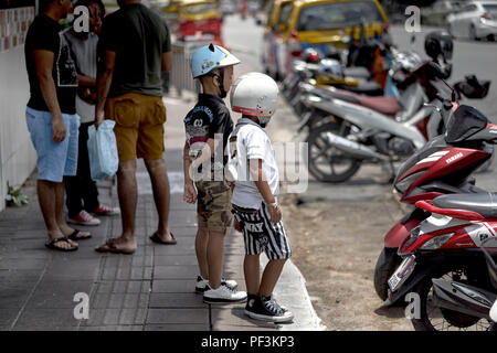Youngster and motorcycle safety helmets - Stock Image