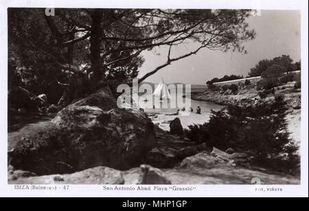 Grassio beach, San Antonio (Sant Antoni de Portmany), Ibiza, Balearic Islands, Spain, with a sailing boat on the water.     Date: circa 1950s - Stock Image
