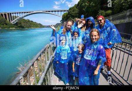 Niagara Falls, USA – August 29, 2018: Happy group tourists in blue raincoats waiting tour boat on Niagara Falls - Stock Image