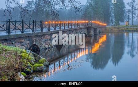 Old stone bridge decorated with lit light bullbs early in the morning by Nääs art gallery outside Gothenburg in Sweden - Stock Image