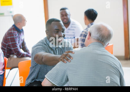 Smiling, happy man talking, comforting man in group therapy - Stock Image