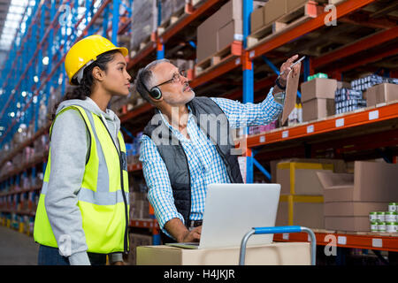 Warehouse manager and female worker interacting while using laptop - Stock Image