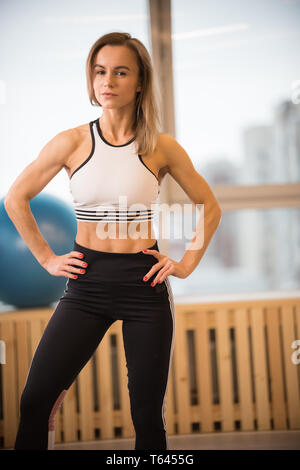 Young athletic woman in a good shape standing posing for the camera in the fitness studio - Stock Image