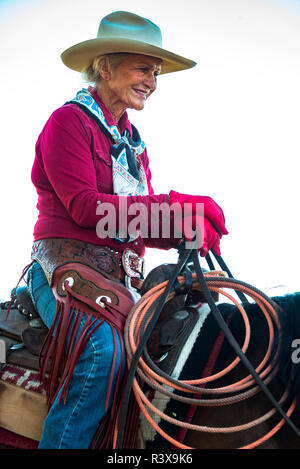 USA, California, Parkfield, V6 Ranch portrait of a smiling cowgirl in a red shirt and hat on a horse (MR) - Stock Image