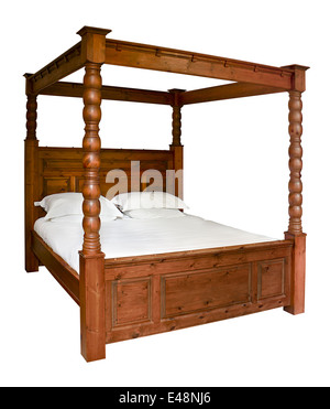 Traditional wooden Four Poster Bed isolated against a white background - Stock Image