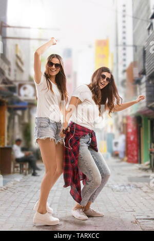 Two young women dancing on street listening to music - Stock Image
