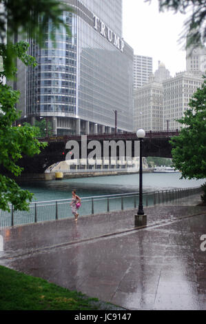 Chicago, United States. 14th Jun,  2017. Girl running along the Chicago Riverwalk as she tries to get out of the - Stock Image