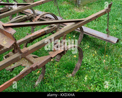 Old tractor powered cultivator on grass close up - Stock Image