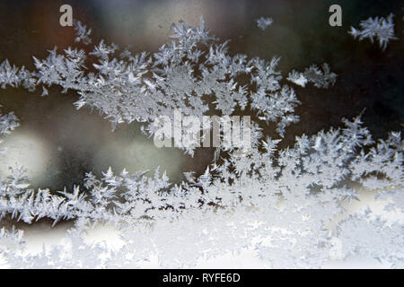 Beautiful ice crystal structures forming on a cold window in winter, a crystaline work of art by Mother Nature - Stock Image