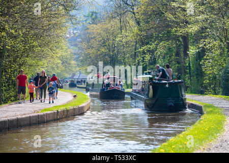 Busy day on the canal near Llangollen with families walking on the tow path and narrow boats taking boat trips, Wales, UK. - Stock Image