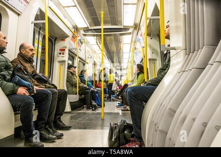 Passengers sitting in a carriage on a London Underground train. - Stock Image